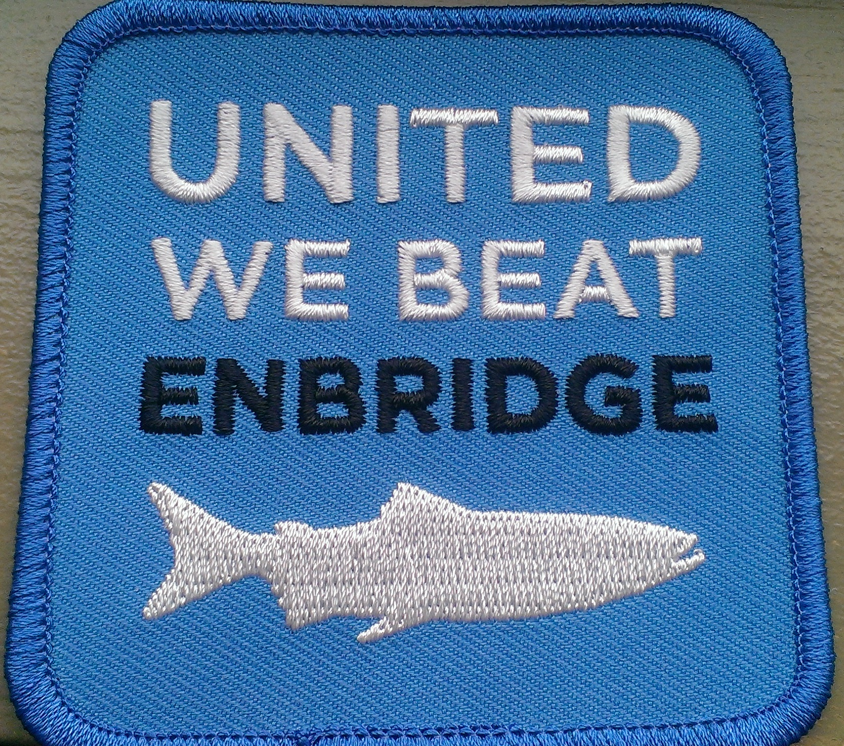 """Light-blue fabric patch with words """"United we beat Enbridge"""""""